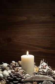 Vela blanca encendida con adornos de piñas
