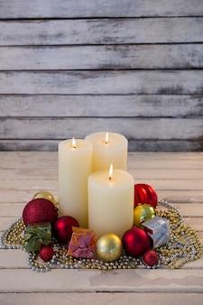 Velas blancas encendidas con decoración navideña