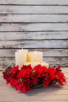 Velas blancas encendidas con flores rojas