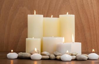 Velas blancas y guijarros de piedra en la madera