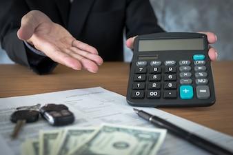 Vendedor de coches con una clave y el cálculo de un precio en la oficina de concesión