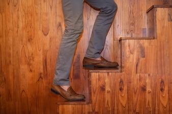 Ver recortada de las piernas del hombre que sube las escaleras de madera