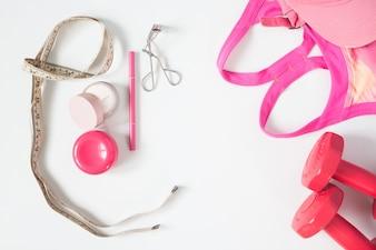 Vista aérea de artículos de belleza esencial, pesas rojas, sujetador de deporte y cosmética, vista superior aislada sobre fondo blanco