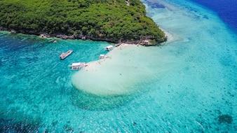Vista aérea de la playa de arena con los turistas nadando en la hermosa agua de mar clara de la playa de la isla de Sumilon aterrizando cerca de Oslob, Cebú, Filipinas. - Aumentar el procesamiento de color.