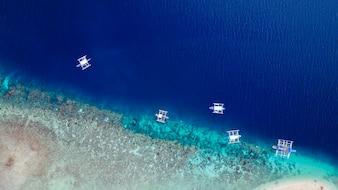 Vista aérea de la playa de arena con los turistas nadando en la hermosa agua de mar claro de la playa de la isla de Sumilon aterrizando cerca de Oslob, Cebú, Filipinas. - Aumentar el procesamiento de color.