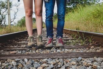 Vista de piernas de pareja de senderistas en vías de tren