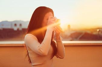 Vista lateral de chica usando su cámara vintage al atardecer