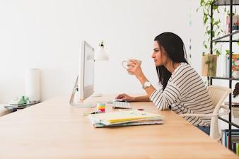 Vista lateral de empresaria trabajando con un ordenador y sujetando una taza
