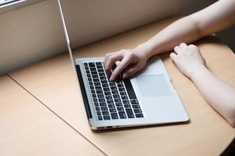 Vista lateral de la mano usando la computadora portátil