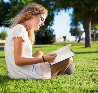 Vista lateral de mujer tranquila leyendo en el parque
