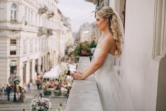 Vista lateral de novia con ramo en el balcón