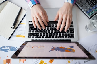 Vista recortada de la persona de negocios trabajando en la computadora portátil