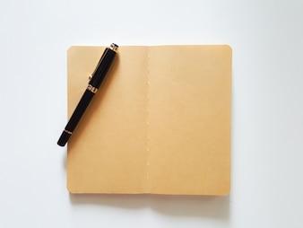 Vista superior abrir el cuaderno y la pluma sobre fondo blanco de escritorio.