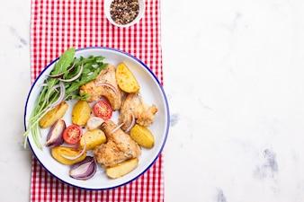 Vista superior de alas de pollo con patatas