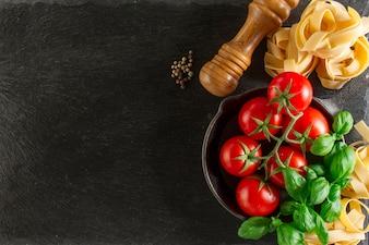 Vista superior de composición fantástica con albahaca, pasta y tomates