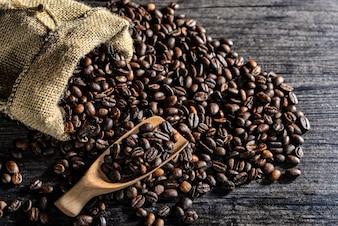 Vista superior de cuchara de madera y bolsa de lona con granos de café