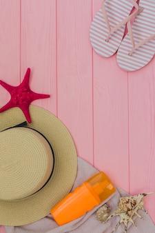 Vista superior de elementos veraniegos sobre superficie de madera rosa