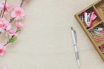 Vista superior de escritorio de oficina de escritorio de fondo. El café de pluma de plata hermosa flor de color rosa de madera clip de grapa sobre tabla de madera backgtound con copia espacio.