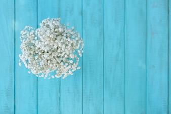 Vista superior de flores blancas bonitas con fondo de tablones de madera azules