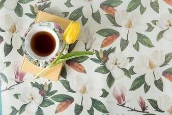 Vista superior de fondo floral con tulipán, libro y taza de té