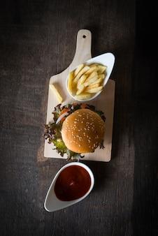 Vista superior de hamburguesa casera rústica y patatas fritas con salsa de tomate.
