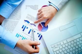 Vista superior de hombres de negocio analizando gráficos de barras y un portátil