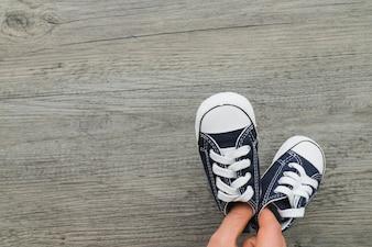 Vista superior de mano con zapatos deportivos