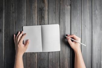 Vista superior de manos con lápiz y un cuaderno abierto