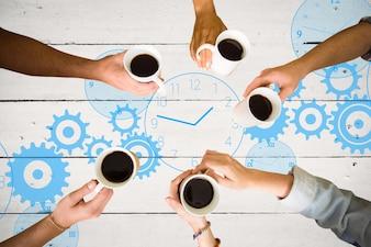 Vista superior de manos sujetando tazas de café con un reloj pintado de fondo
