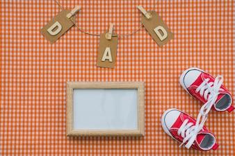 Vista superior de marco en blanco y zapatos para el día del padre
