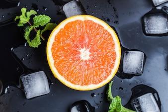 Vista superior de media naranja con hielo y hierbabuena