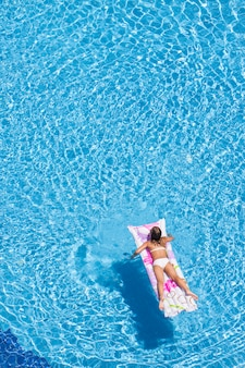 Vista superior de mujer en la piscina con una colchoneta