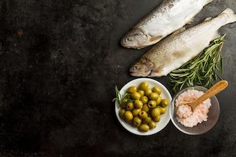 Vista superior de pescado, aceitunas y planta aromática