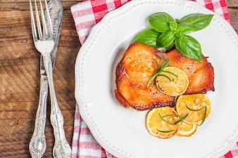 Vista superior de pollo cocinado junto a un cuchillo y un tenedor