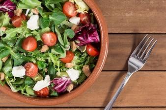 Vista superior de tenedor junto a un plato con ensalada