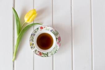 Vista superior de tulipán amarillo con taza de té