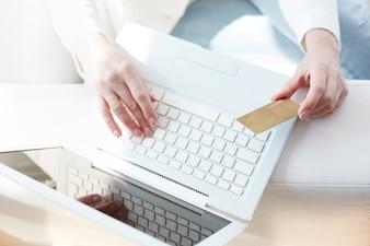 Vista superior de un portatil y una tarjeta de crédito