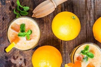 Vista superior de zumos con un exprimidor y naranjas