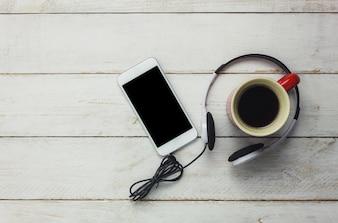 Vista superior smartphone y auriculares con taza de café