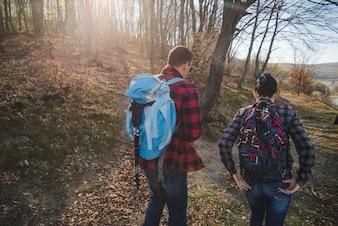 Vista trasera de excursionistas con mochilas caminando