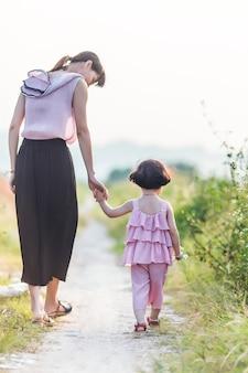 Vista trasera de madre paseando con su hija