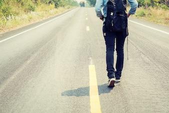 Vista trasera de mujer caminando por la carretera