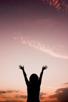 Vista trasera de mujer con las manos levantadas mirando al cielo