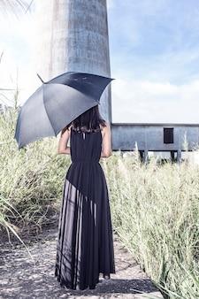 Vista trasera de mujer con vestido negro y paraguas