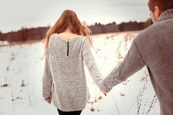 Vista trasera de mujer rubia paseando con su novio sobre la nieve
