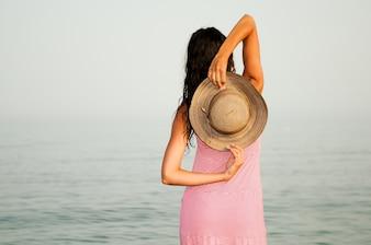 Vista trasera de mujer sosteniendo su sombrero