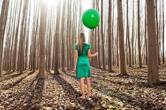 Vista trasera de mujer sujetando un globo verde en el bosque