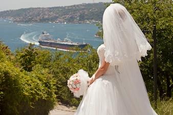 Vista trasera de novia con ramo mirando la bahía