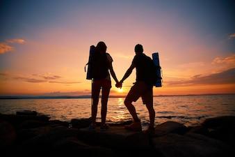 Vista trasera de pareja disfrutando de la puesta de sol