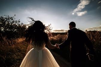 Vista trasera de recién casados caminando al atardecer